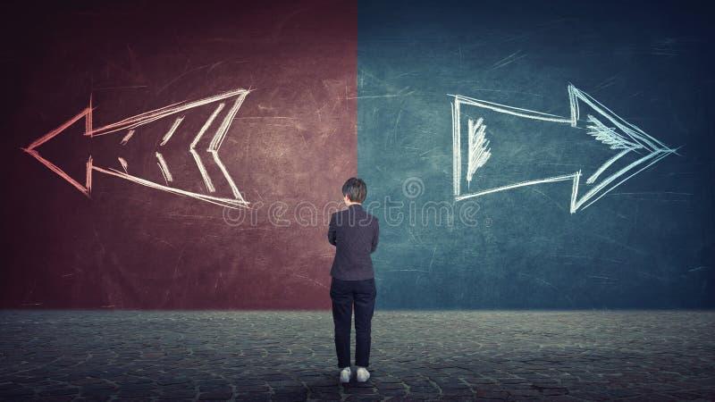 在分裂墙壁前面的半信半疑的女实业家作为箭头带领用红色两个的不同的方式和蓝色边 左正确的选择或 免版税库存图片