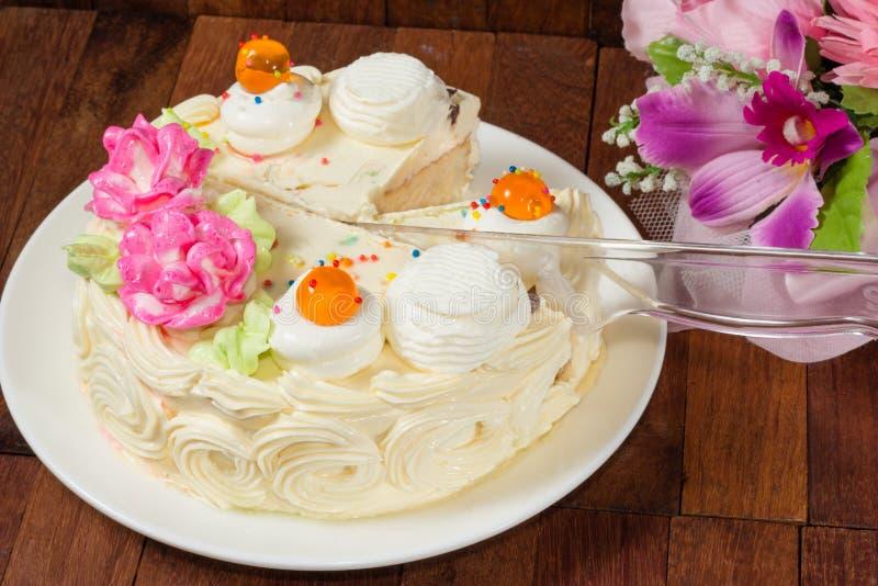 在切口的奶油色蛋糕与塑料刀子 免版税库存图片