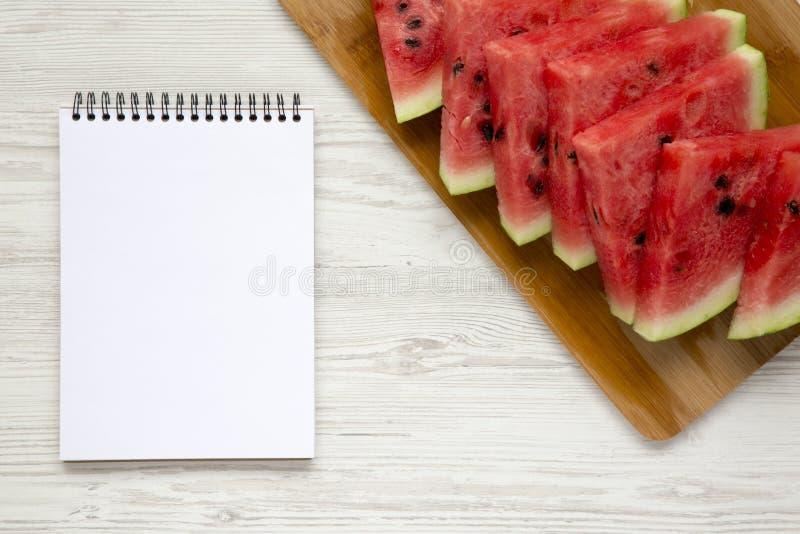 在切口竹委员会的Liced新鲜的西瓜有在白色木表面,顶视图的空白的笔记薄的 免版税库存图片