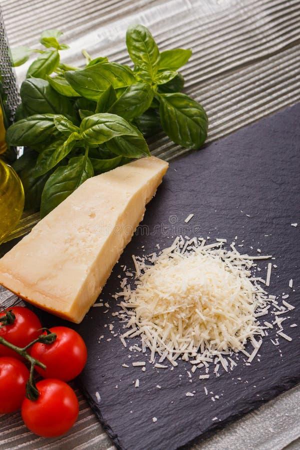 在切委员会的板岩石头的芬芳被磨碎的巴马干酪 免版税库存图片