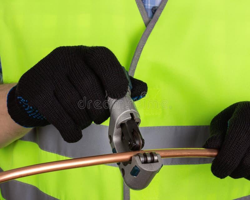 在切开有切管机的黑手套的大师一个铜管子 库存图片