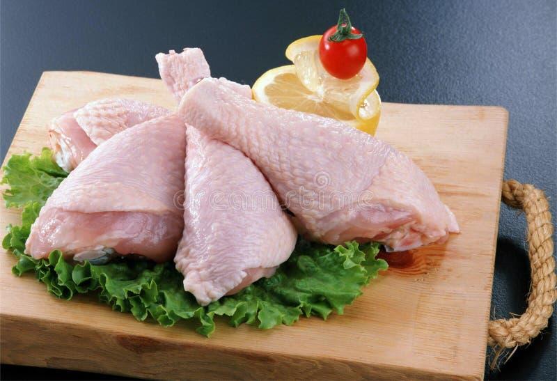 在切板的木鸡大腿在乳酪、蕃茄和绿色旁边 免版税库存图片