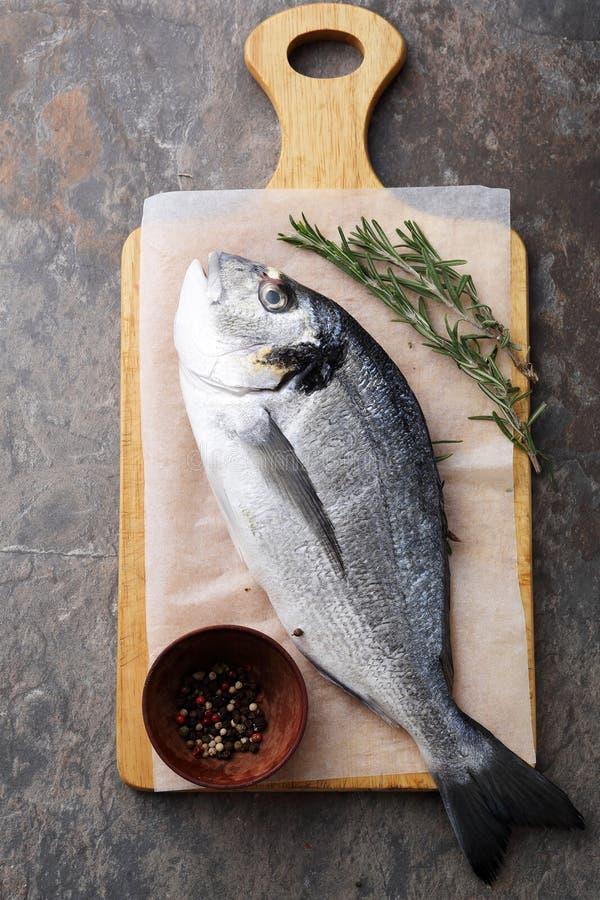 在切板的未加工的dorada鱼 免版税库存图片