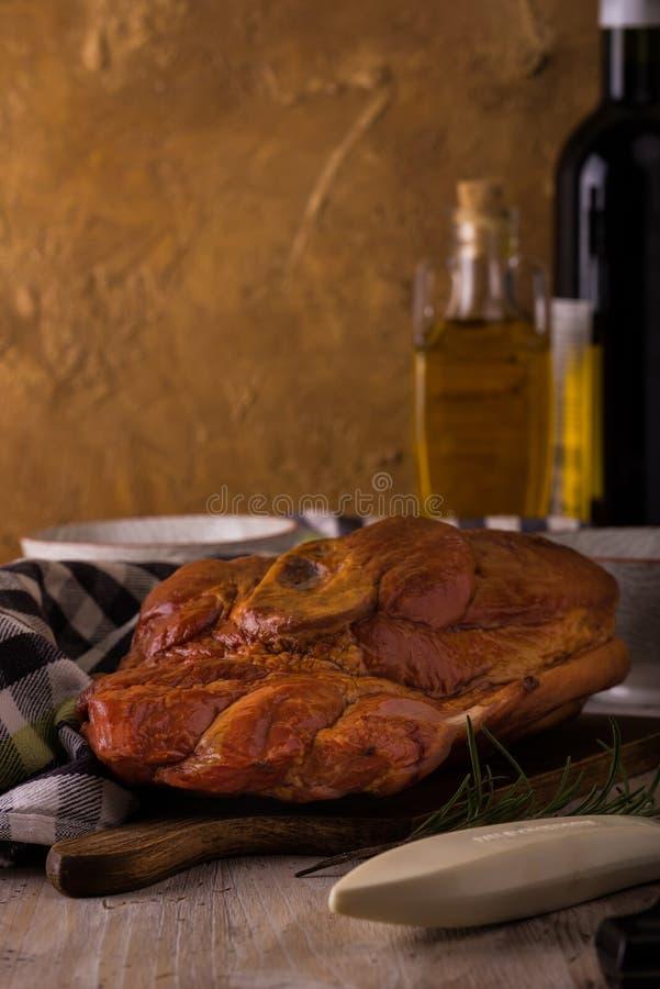 在切板的熏制的猪肉有厨房器物和瓶的 库存照片