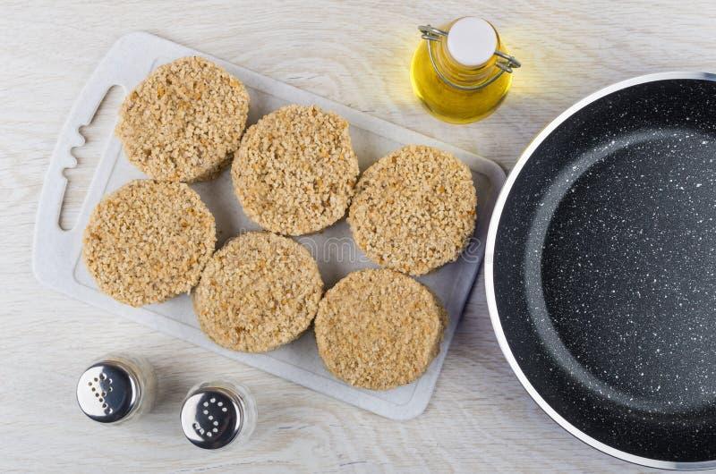在切板,油,胡椒,盐,煎锅的未加工的炸肉排 免版税库存图片