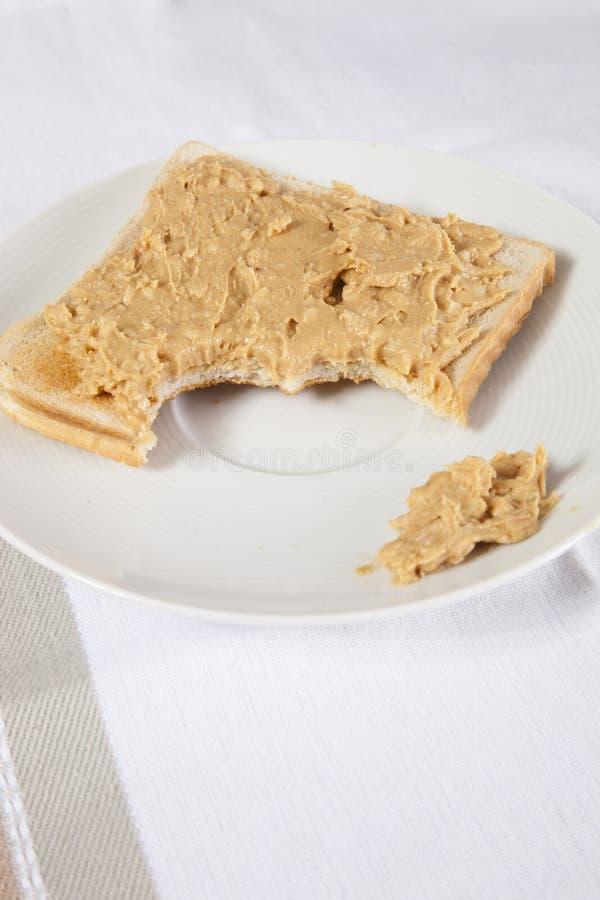 在切片的花生酱被咬住的面包 免版税库存图片