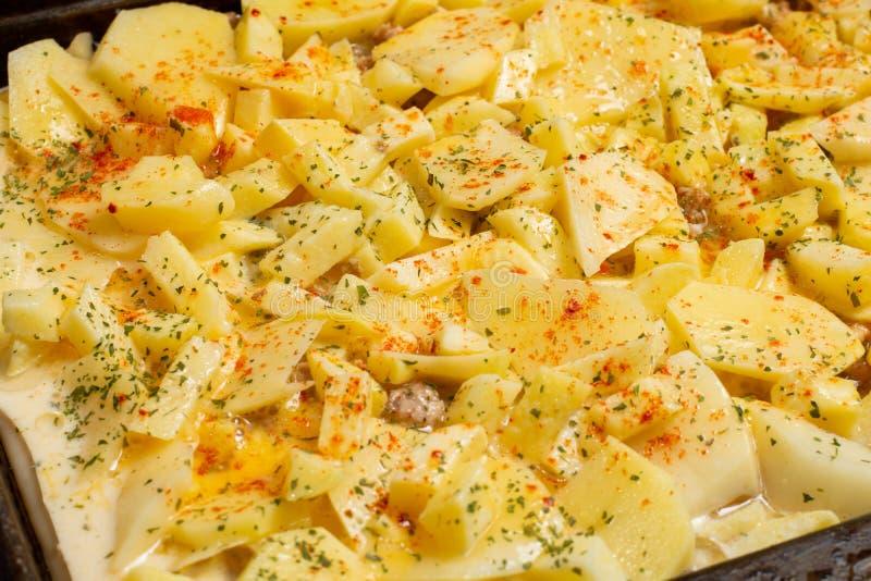在切的未加工的土豆上的平的位置用肉末和菜 免版税图库摄影