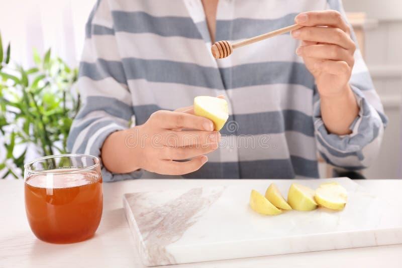 在切的苹果上的妇女倾吐的蜂蜜 免版税库存照片