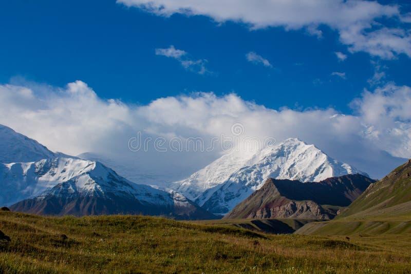 在列宁峰顶附近的帕米尔山冷的雪冰冰川墙壁 库存照片