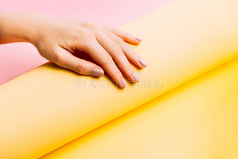 在创造性的桃红色和黄色背景的美好的妇女修指甲 最低纲领派趋向 库存图片