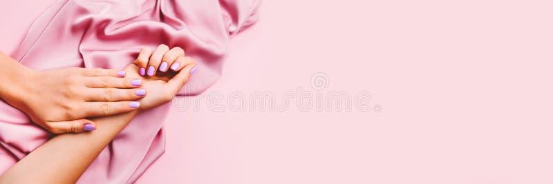 在创造性的桃红色背景的美好的妇女修指甲与丝织物 最低纲领派趋向 免版税库存图片