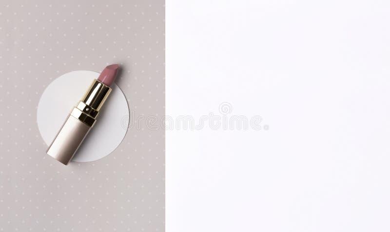 在创造性的裸体粉色口红圆点与拷贝空间的米黄背景 免版税库存照片