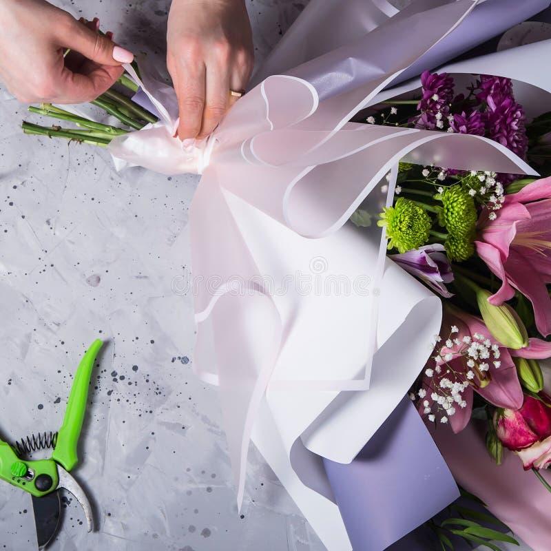 在创造花束过程中的卖花人的工作用百合在工作场所 免版税库存图片