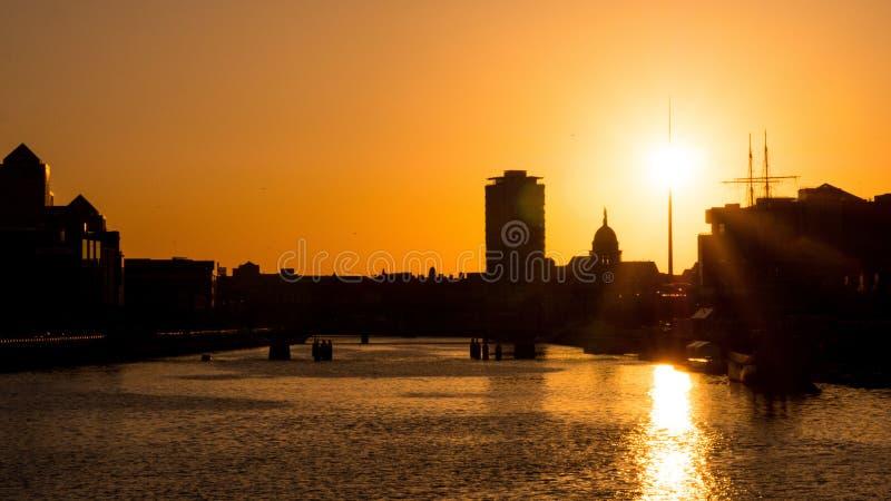 在利菲河的美好的生动的日落在都伯林,有太阳的爱尔兰直接地在尖顶和现出轮廓的大厦后 免版税图库摄影