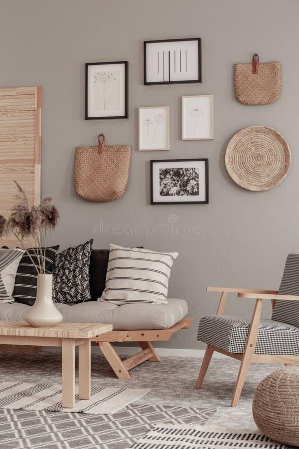 在别致的斯堪的纳维亚沙发旁边的时髦葡萄酒扶手椅子有在优等的客厅内部的枕头的 库存照片