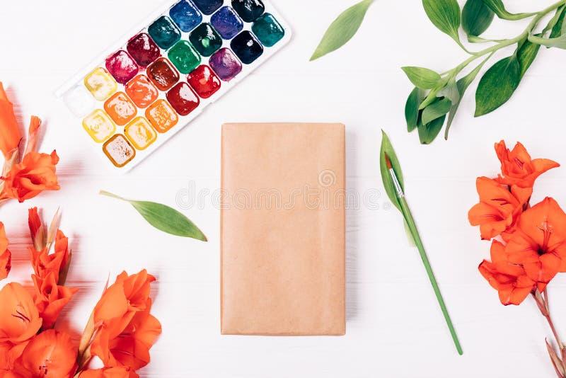 在制作纸包裹的空白的礼物盒在水彩油漆旁边 免版税库存照片