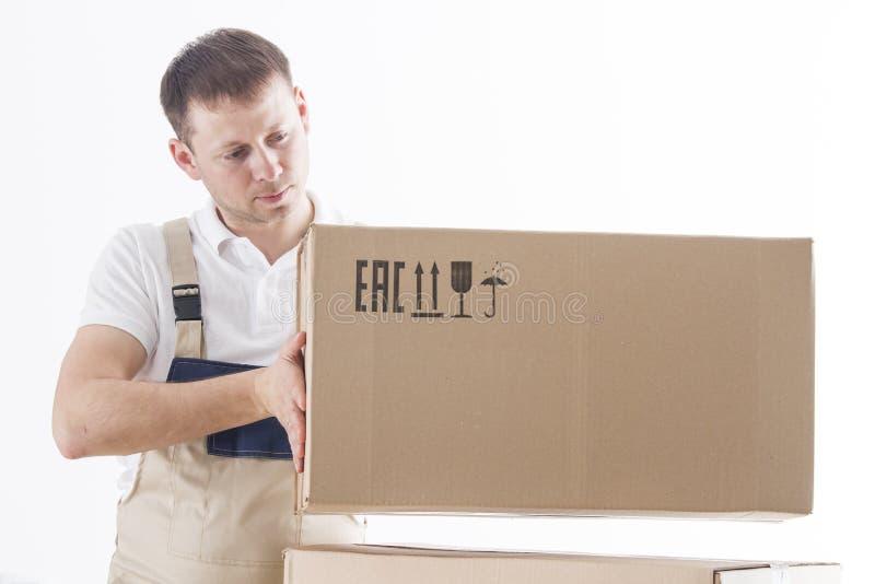在制服的装载者在白色背景上把被隔绝的纸板箱放 白种人男性拆迁服务工作者拿着箱子 免版税库存照片