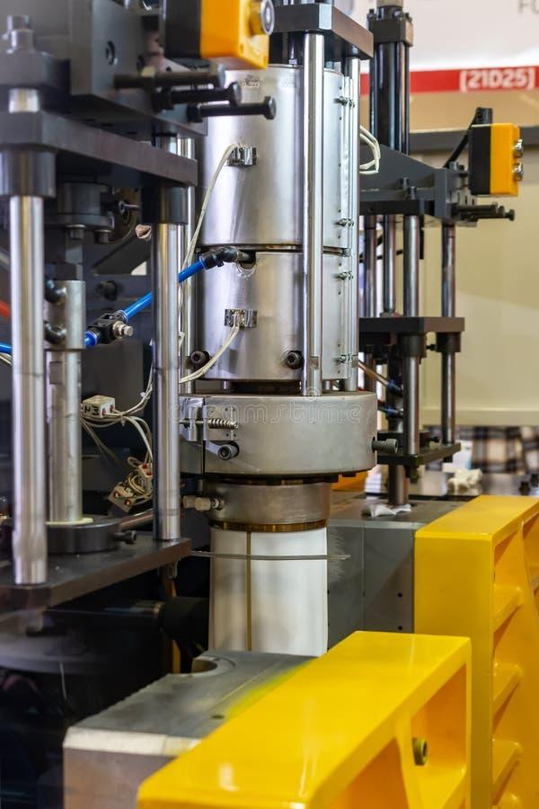 在制造产品过程中的被铸造的塑料机器 免版税库存图片