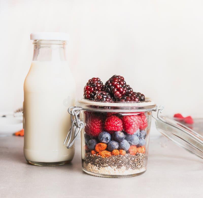 在制玻璃的健康早餐用燕麦粥、Chia种子、Goji莓果、新鲜的莓果和瓶牛奶,正面图 免版税库存照片