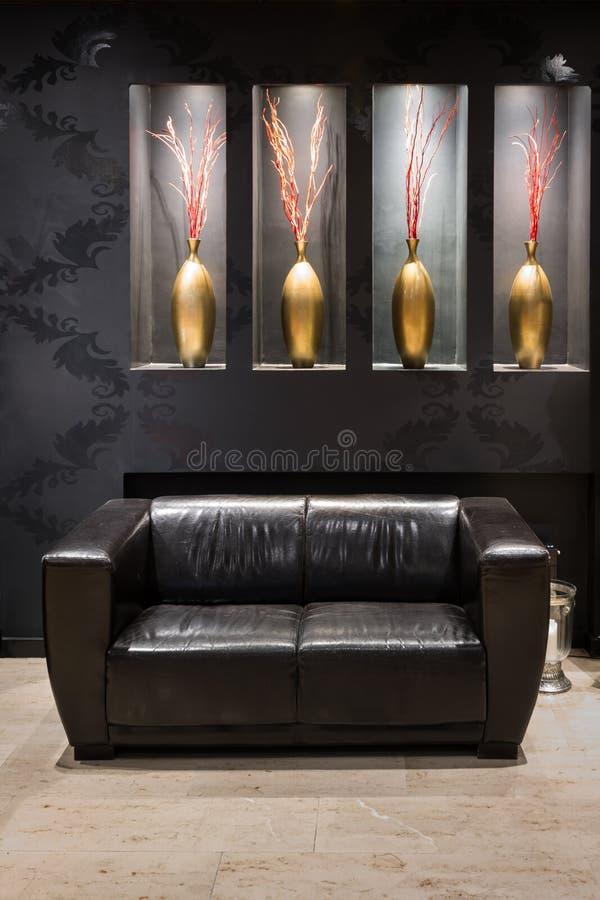 在前室的黑皮革长沙发 免版税图库摄影