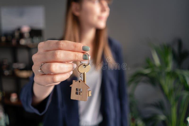 在前景房子钥匙在妇女手上 年轻俏丽的妇女 现代轻的大厅内部 不动产,抵押权 免版税库存照片