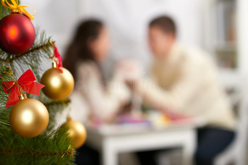 在前景的圣诞树与defocused浪漫年轻夫妇坐在桌、愉快的人民和爱概念,新年holida上 免版税库存图片