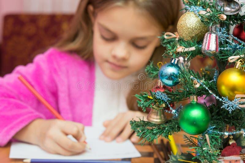 在前景的圣诞树,在背景中写信的女孩 库存照片