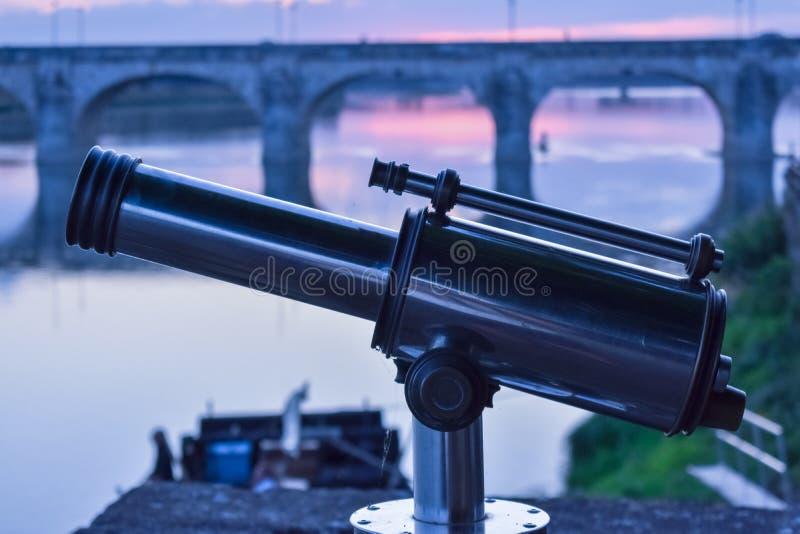 在前景的在日落背景的小望远镜和桥梁 库存照片