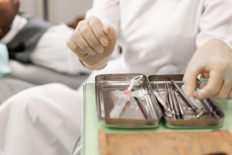 在前景的牙齿仪器 对待在牙齿诊所的妇女牙医根管 说谎人的患者  库存图片