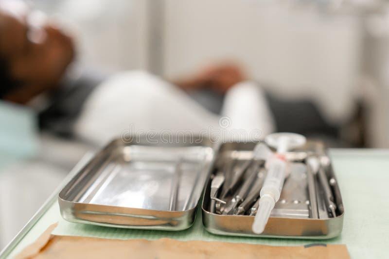 在前景的牙齿仪器 对待在牙齿诊所的妇女牙医根管 说谎人的患者  免版税库存照片