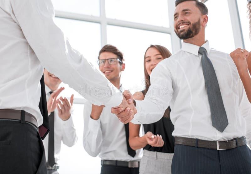 在前景 握手商人在办公室 免版税库存照片