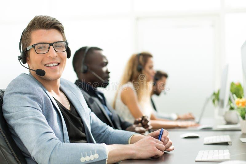 在前景 雇员电话中心在办公室 免版税库存图片