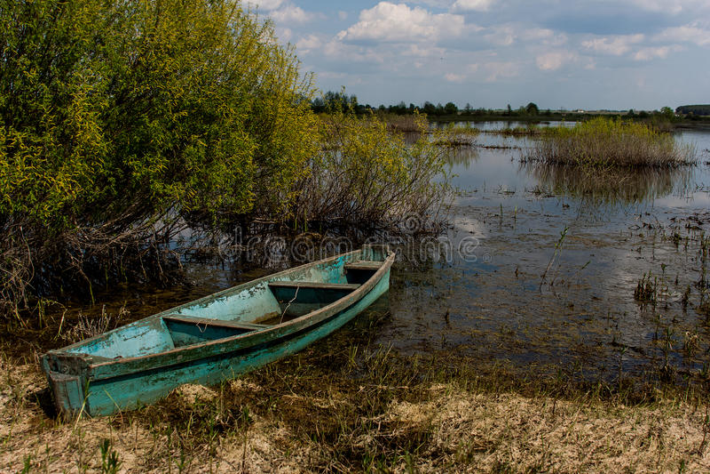 在前河的沼泽的河岸的一条老小船 库存图片