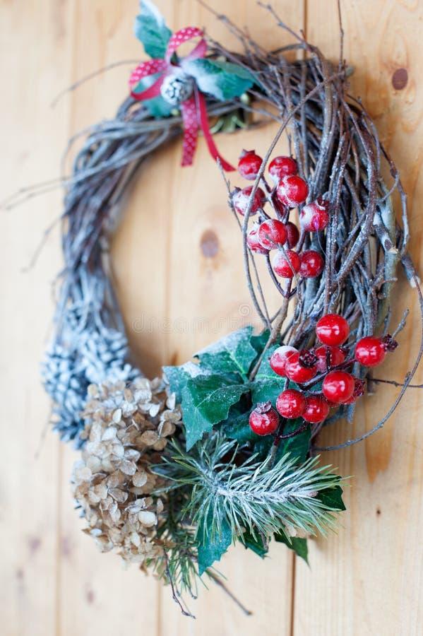 在前面木门的自创圣诞节花圈特写镜头 库存图片