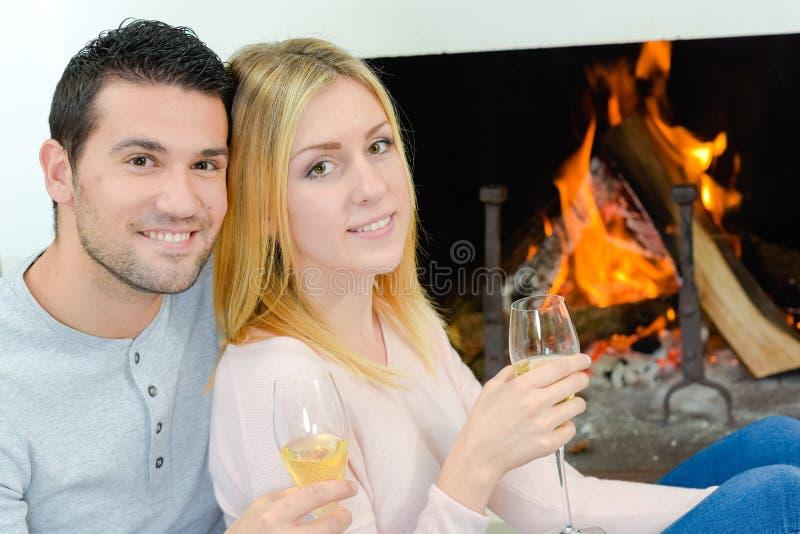 在前面火的夫妇饮用的酒 免版税库存照片