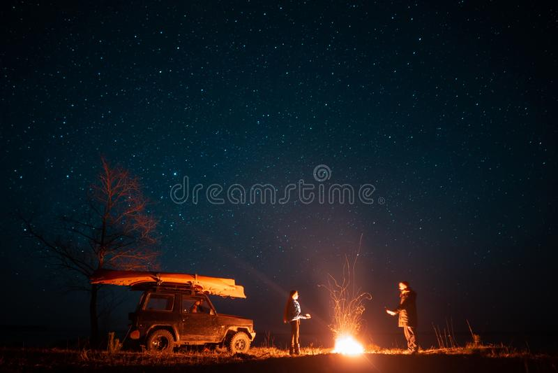 在前面灼烧的篝火的愉快的夫妇男人和妇女身分 库存图片