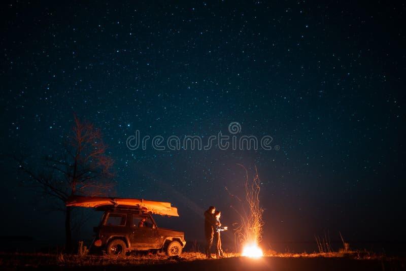 在前面灼烧的篝火的愉快的夫妇男人和妇女身分 库存照片