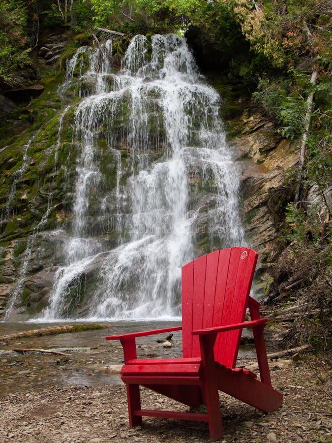 在前面La滑道瀑布的红色椅子 库存图片