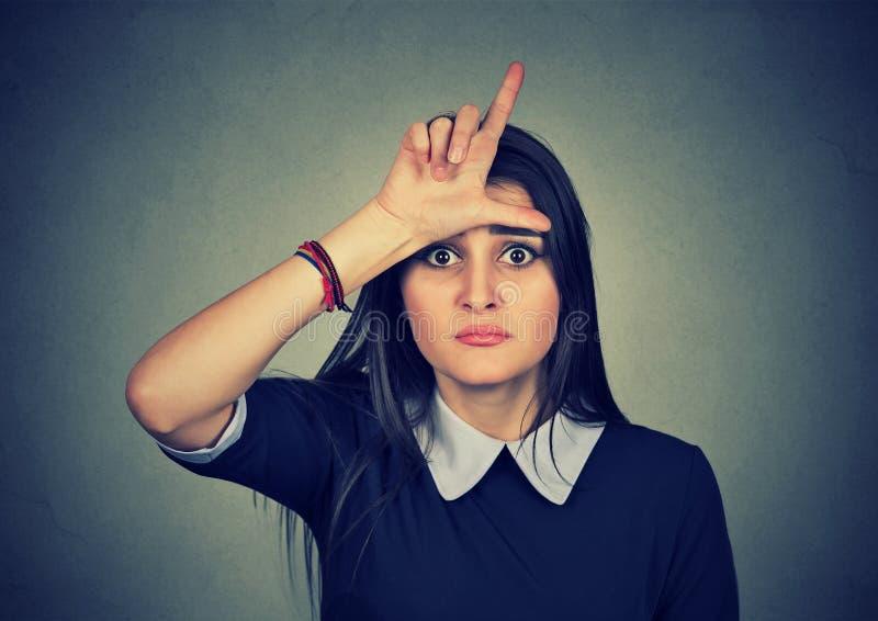 给在前额的年轻不快乐的妇女失败者标志 免版税库存图片