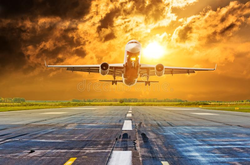 在剧烈的云彩上的商业飞机飞行跑道机场 免版税库存图片