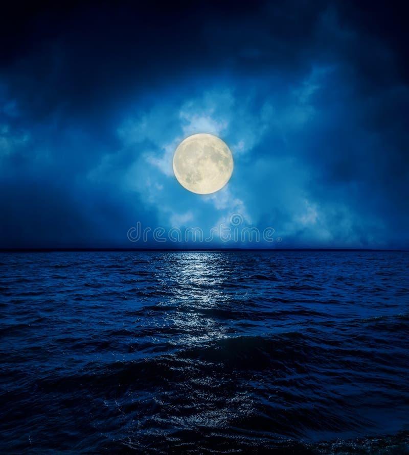 在剧烈的云彩的满月在黑暗的水 免版税库存照片