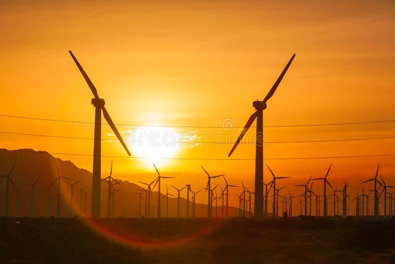在剧烈的日落天空的现出轮廓的风轮机 库存图片