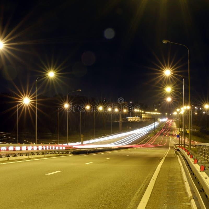 在剧烈的日落定期的光的速度交通在机动车路高速公路落后在晚上,长的曝光摘要都市背景 库存图片