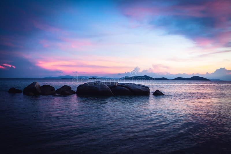 在剧烈的日落期间在紫色c,热带海滩假日环境美化与镇静绿松石海和大圆的石头和岩石在海 库存图片