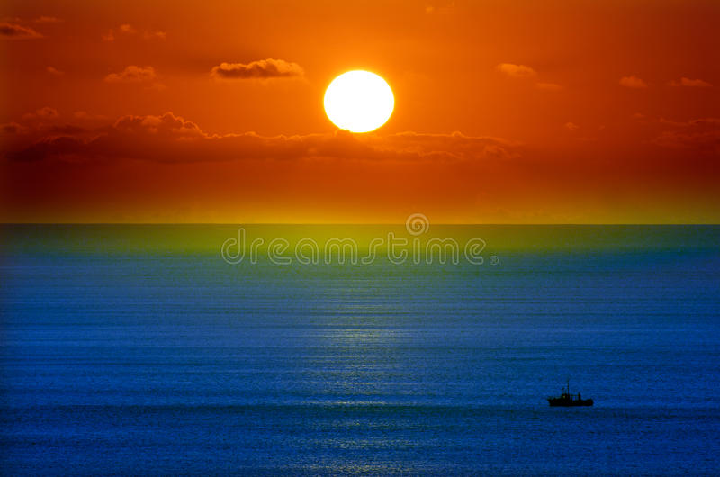 在剧烈的日落期间的五颜六色的海景与一艘捕鱼船 图库摄影