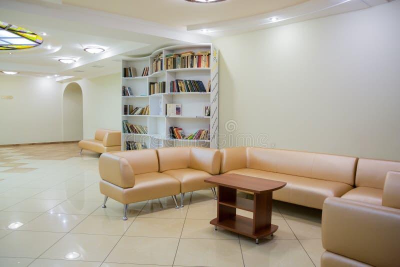 在剧院的大厅的内部年轻观众的 在架子的书,被布置的皮革家具 免版税库存图片