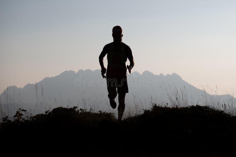 在剪影的山赛跑者在一个暗示风景 库存照片