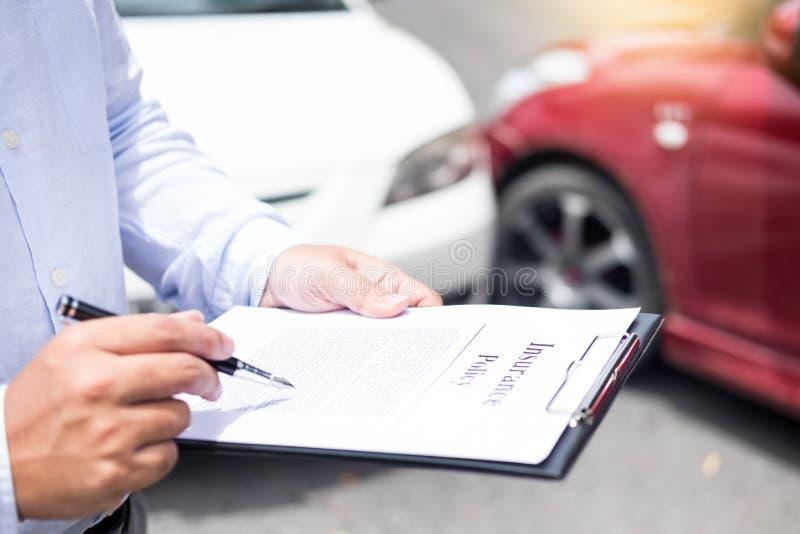 在剪贴板的保险代理公司文字,当审查汽车在被估计和被处理时的事故要求以后 免版税图库摄影