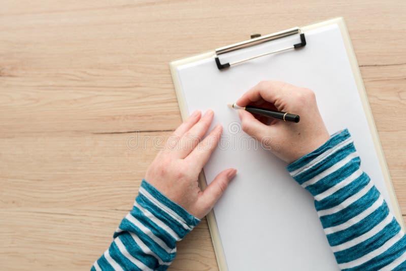 在剪贴板笔记本纸的妇女文字 免版税图库摄影