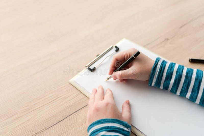 在剪贴板笔记本纸的妇女文字 库存照片